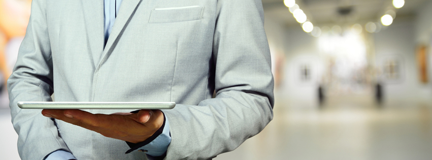 Business Man using Mobile Tablet in Gallery Art Center or Museum.  Selective Focus on Tablet and Hand.