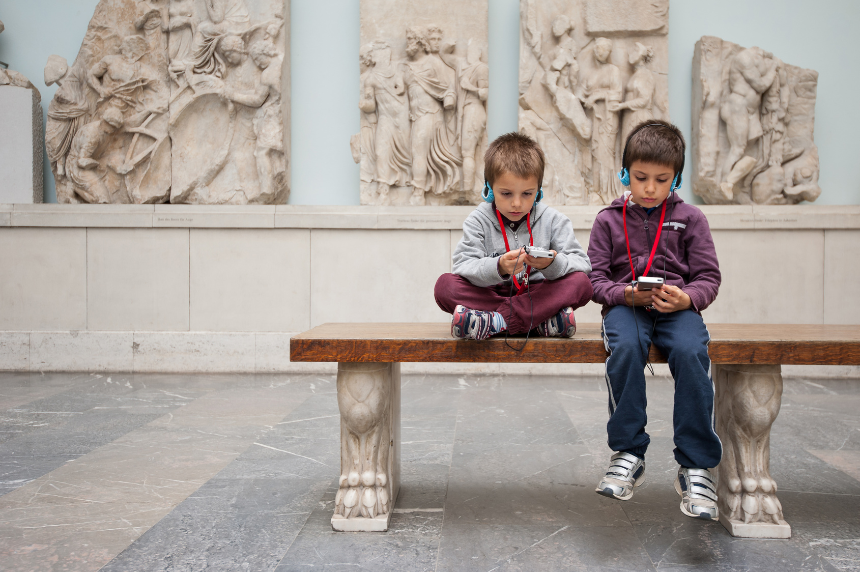 Kids inside Pergamon Museum listening to audio guide. Berlin, Germany.