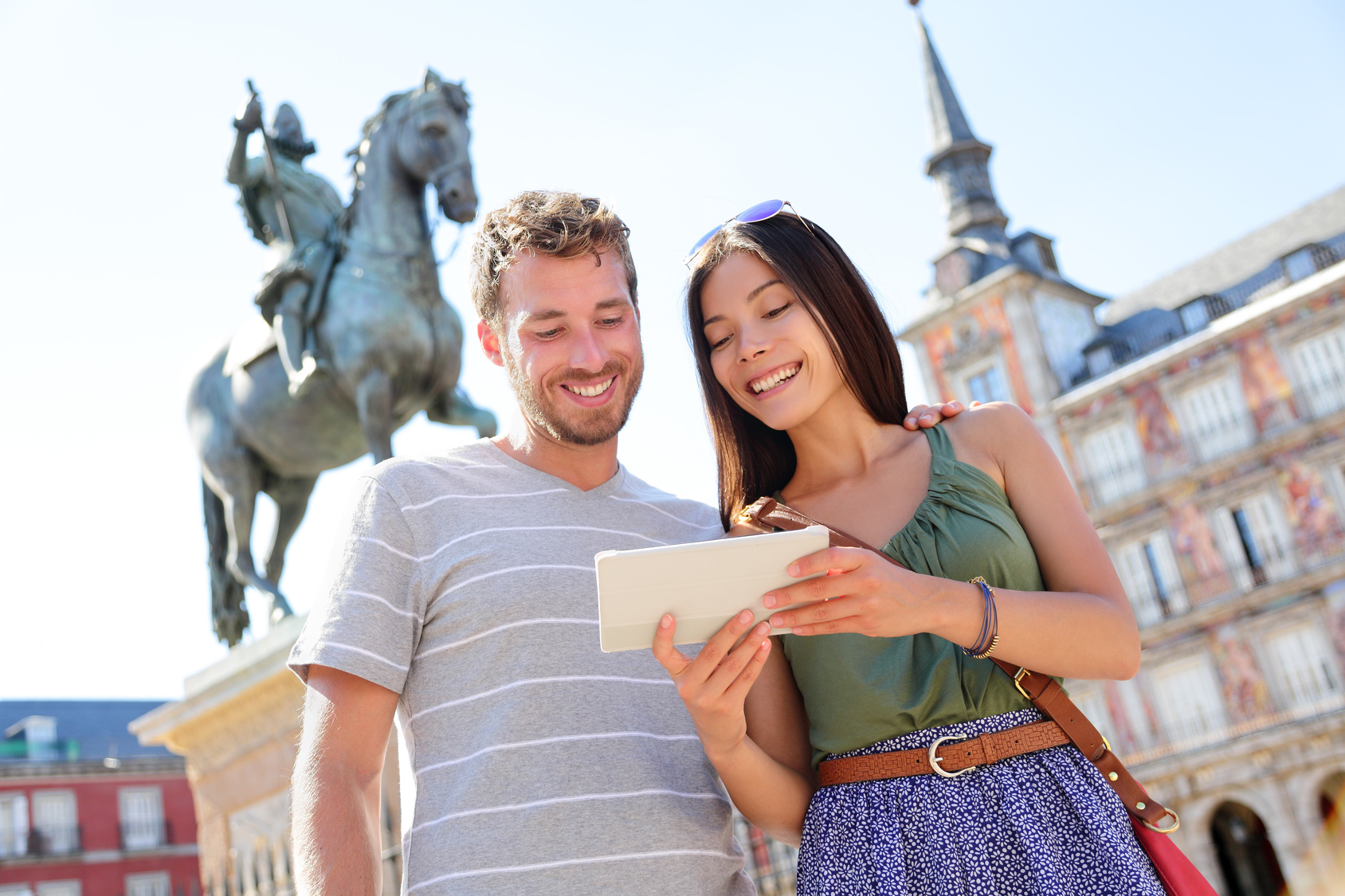 Madrid tourists using tablet travel app guidebook ebook on Plaza Mayor by statue of King Philip III. Tourist couple sightseeing visiting tourism landmarks and attractions in Spain. Young woman and man